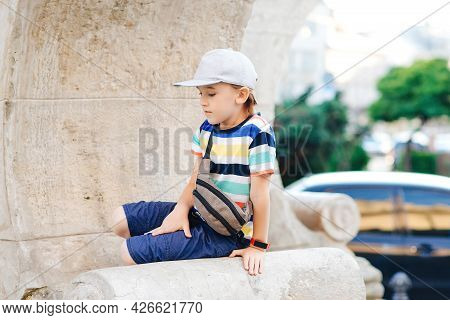 Cute Fashionable Boy Walking The City. Happy Child Wearing Trendy Casual Clothes And Waist Bag. Summ