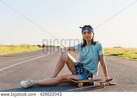 Beautiful Dark Haired Woman Wearing T Shirt, Short And Shoes Sitting Near Surf Skate On The Asphalt