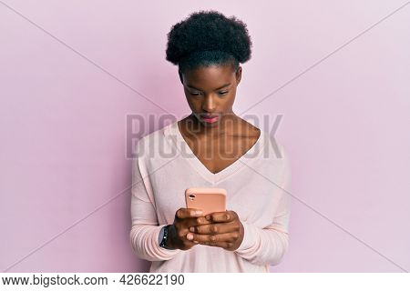 Young african american girl using smartphone relaxed with serious expression on face. simple and natural looking at the camera.