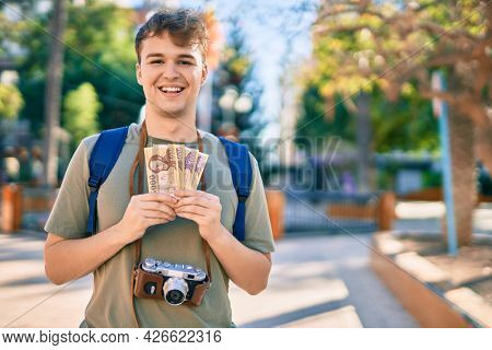 Young caucasian tourist man using vintage camera holding hungarian forint at the city.