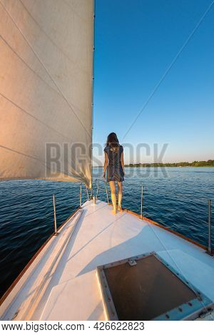 Travel On A Yacht. The Girl Stands On The Bow Of The Ship And Looks Into The Distance. Rest On The D