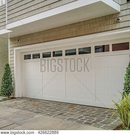 Square Two Storey Houses In Long Beach With Glass Paned Garage Doors At The Facade