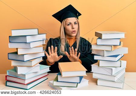 Young caucasian woman wearing graduation ceremony robe sitting on the table moving away hands palms showing refusal and denial with afraid and disgusting expression. stop and forbidden.