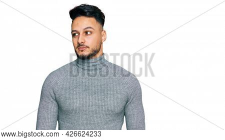 Young arab man wearing casual clothes smiling looking to the side and staring away thinking.
