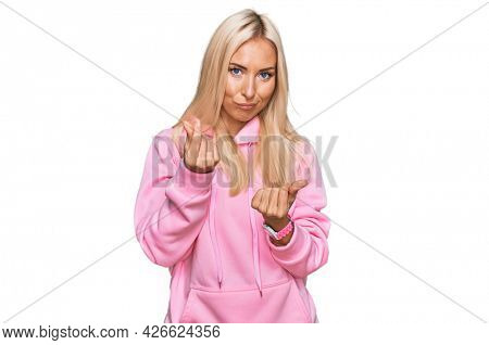 Young blonde woman wearing casual sweatshirt doing money gesture with hands, asking for salary payment, millionaire business