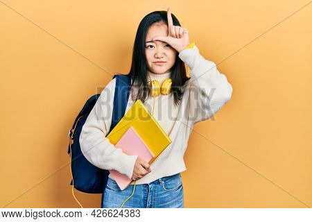 Young chinese girl holding student backpack and books making fun of people with fingers on forehead doing loser gesture mocking and insulting.
