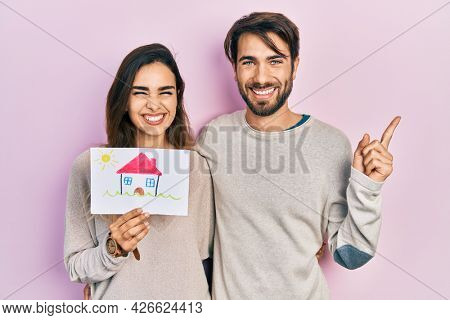 Young hispanic couple holding house draw smiling happy pointing with hand and finger to the side
