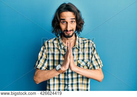 Young hispanic man wearing casual clothes praying with hands together asking for forgiveness smiling confident.