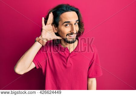 Young hispanic man wearing casual clothes smiling with hand over ear listening and hearing to rumor or gossip. deafness concept.