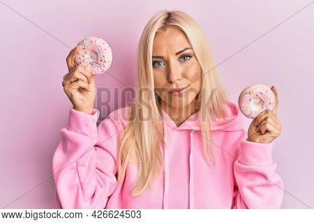 Young blonde woman holding tasty pink doughnuts over eyes relaxed with serious expression on face. simple and natural looking at the camera.