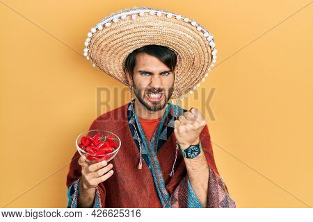 Young hispanic man wearing mexican hat holding chili annoyed and frustrated shouting with anger, yelling crazy with anger and hand raised
