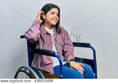 Young brunette woman sitting on wheelchair smiling with hand over ear listening an hearing to rumor or gossip. deafness concept.