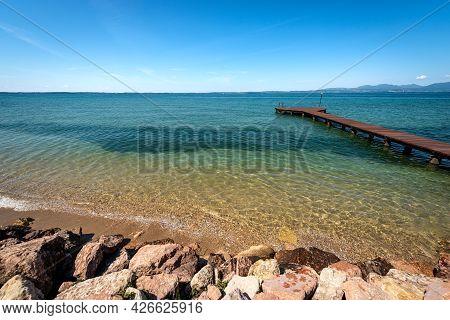 Beautiful Beach With A Small Empty Wooden Pier On Lake Garda (lago Di Garda) Between The Small Villa