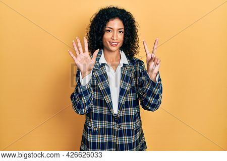 Young latin girl wearing business clothes showing and pointing up with fingers number seven while smiling confident and happy.