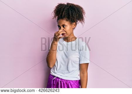 Beautiful african american woman with afro hair wearing sportswear smelling something stinky and disgusting, intolerable smell, holding breath with fingers on nose. bad smell