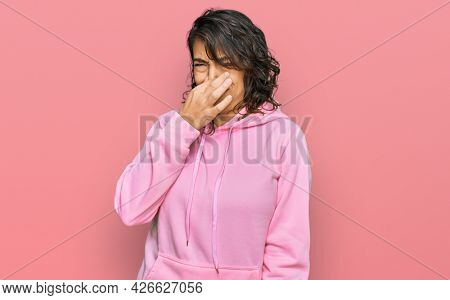 Young hispanic woman wearing casual sweatshirt smelling something stinky and disgusting, intolerable smell, holding breath with fingers on nose. bad smell