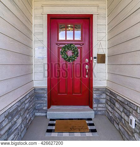 Square Home Entrance With Vibrant Red Glass Paned Front Door Decorated With Wreath