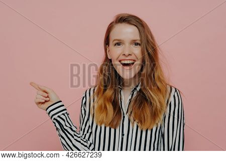 Look Here. Laughing Young Female Pointing Aside At Copy Space For Advertisement With Forefinger, Exp