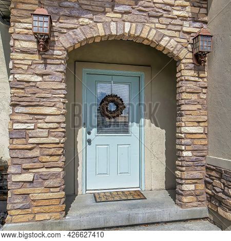 Square Arched Stone Exterior Entryway And Glass Paned Front Door Decorated With Wreath