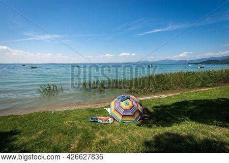 Beautiful Beach With Green Lawn And A Multi Coloured Umbrella On Lake Garda (lago Di Garda) Between