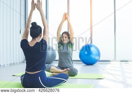 Happy Smiling Healthy Middle-aged Woman Practicing Yoga In Sports Club With Her Growing Daughter.fit
