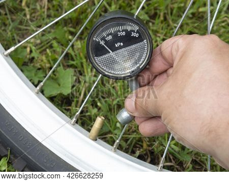 Measuring The Air Pressure In A Bicycle Tire. Bicycle Tours. Bicycle Maintenance