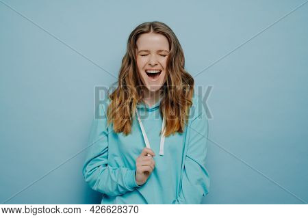 Portrait Of Optimistic Teenage Girl In Casual Clothes With Tongue Piercing Keeping Eyes Closed And L