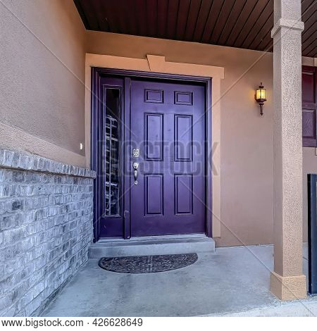 Square Entrance Of Home With Stairs Leading To Porch And Purple Front Door With Wreath