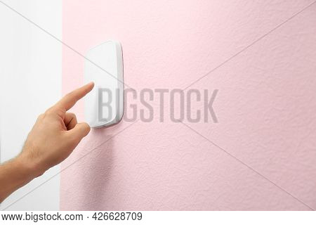 Young Man Entering Code On Alarm System Keypad Indoors, Closeup
