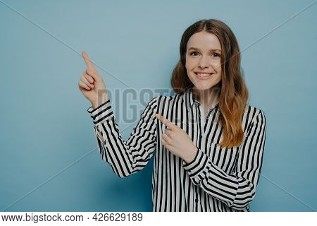 Cute Teenage Girl In Striped Shirt With Shining Smile Pointing Up With Forefingers At Copy Space For