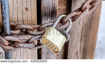 Pano Combination Padlock And Rusty Iron Chain Securing The Door Of Outdoor Bathroom