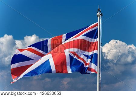 Union Jack Flag. Close-up Of A National Uk Flag With Flagpole, Blowing In The Wind On A Blue Sky Wit