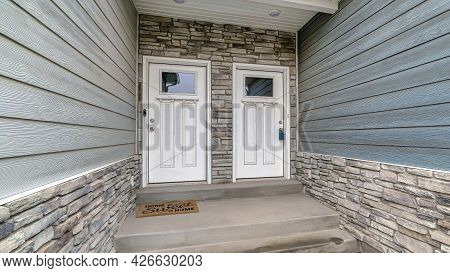 Pano Identical White Wooden Front Doors With Glass Panes Against Stone Brick Wall