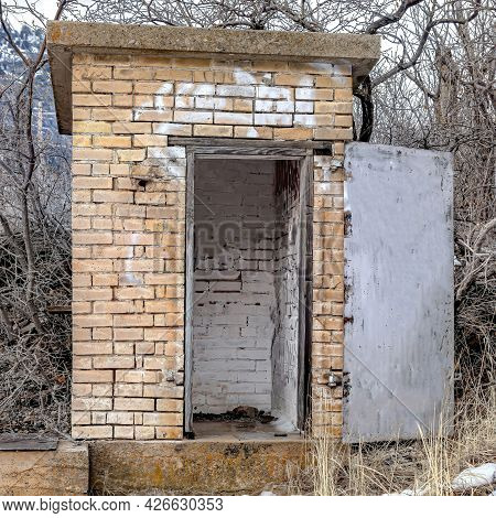 Square Old Abandoned Public Restroom In The Mountain Surrounded By Leafless Brown Trees