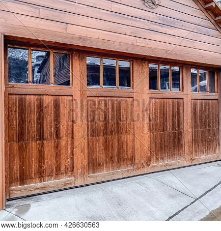 Square Attached Two Car Garage Of Home With Glass Paned Wooden Door Viewed In Winter
