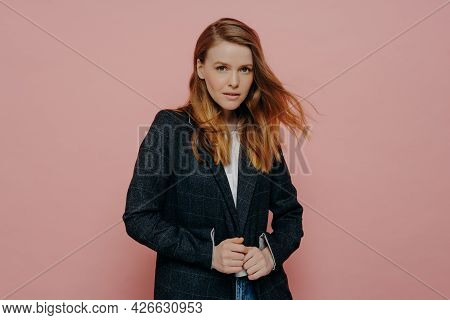 Medium Shot Of Attractive Woman With Ginger Hair Looking At Camera Wearing Dark Formal Jacket And Wh