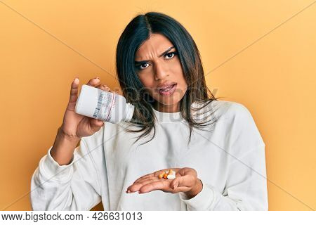 Young latin transsexual transgender woman holding pills in shock face, looking skeptical and sarcastic, surprised with open mouth