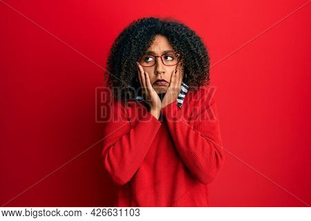 Beautiful african american woman with afro hair wearing sweater and glasses tired hands covering face, depression and sadness, upset and irritated for problem