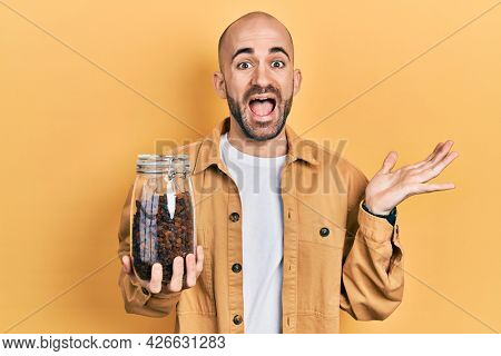 Young bald man holding jar of raisins celebrating achievement with happy smile and winner expression with raised hand