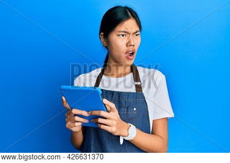 Young chinese woman wearing cook apron using touchpad angry and mad screaming frustrated and furious, shouting with anger. rage and aggressive concept.