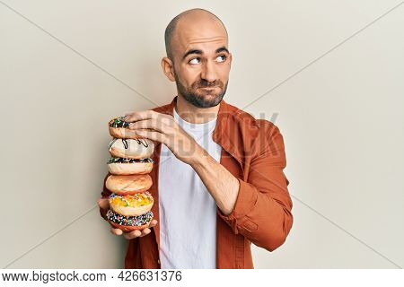 Young hispanic man holding pile of tasty colorful doughnuts smiling looking to the side and staring away thinking.