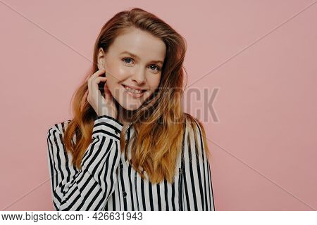 Beautiful Young Female In Stripy Black And White Blouse With Wavy Ginger Medium Length Hair Touching