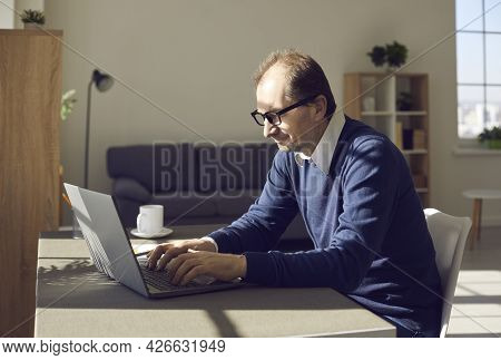 Side View On Mature Man In Eyewear Working On Laptop Remotely At Home Office