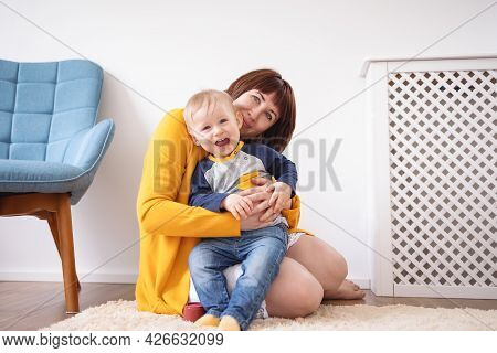 Young Mother Embracing Her Cute Son Carefully