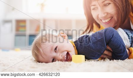 Mother Playing With Her Cute Son On The Floor