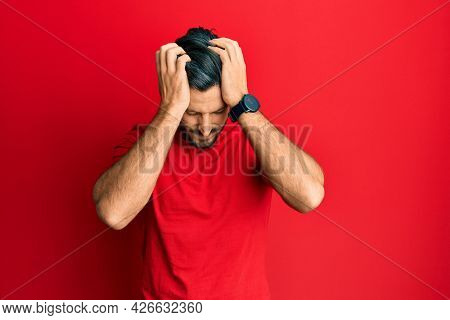 Young hispanic man wearing casual red t shirt suffering from headache desperate and stressed because pain and migraine. hands on head.