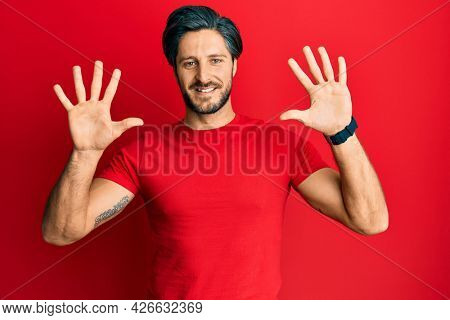 Young hispanic man wearing casual red t shirt showing and pointing up with fingers number ten while smiling confident and happy.