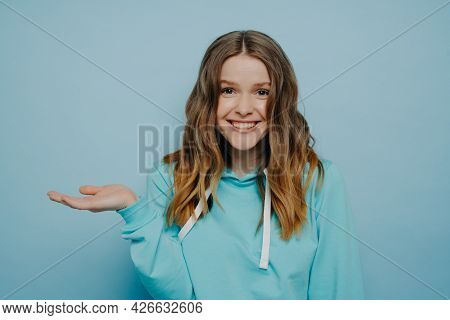 Smiling Teenage Girl With Tipping Hand Shrugging Shoulders Standing Against Light Blue Background, C