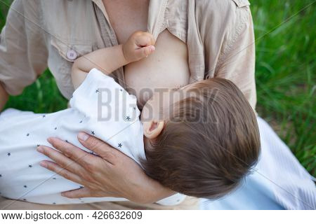 Baby Boy Sucking Milk From Mothers Breast. Portrait Of Mom And Baby.