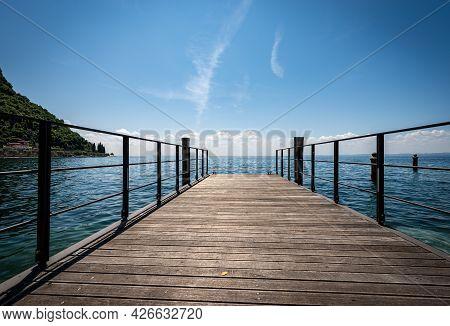 Small Empty Wooden Pier On Lake Garda (lago Di Garda) In Front Of The Small Town Of Garda, Tourist R